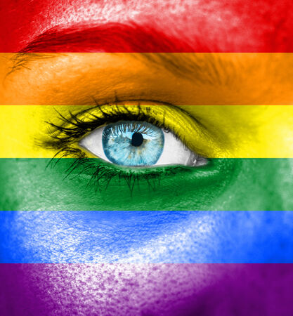 Woman face painted with flag of Pride photo