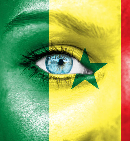 Woman face painted with flag of Senegal photo
