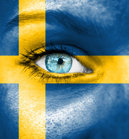 Woman face painted with flag of Sweden photo