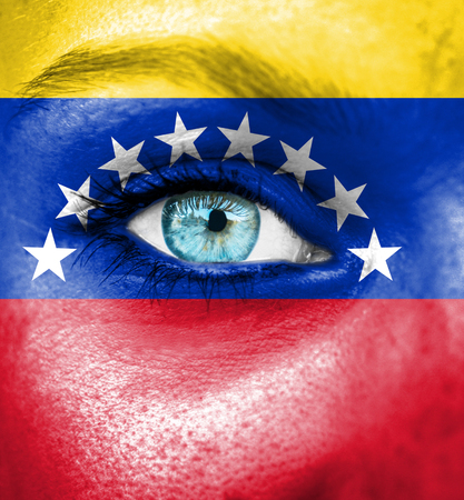 Woman face painted with flag of Venezuela photo