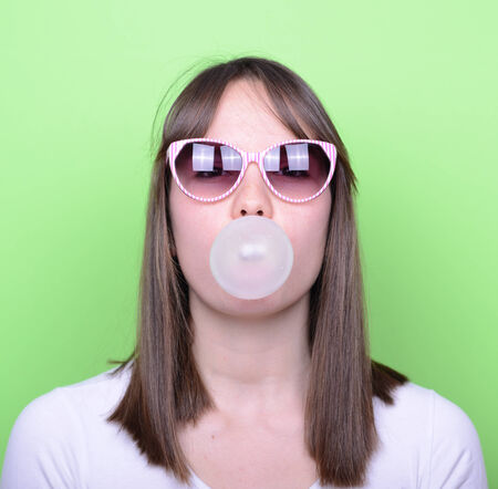 blowing bubbles: Portrait of girl with retro glasses making balloon with bubble gum against green background