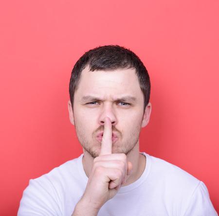 admonester: Portrait de l'homme avec le geste de silence sur fond rouge