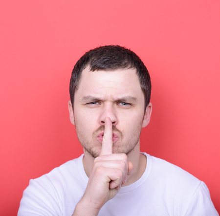conspiratorial: Portrait of man with gesture for silence against red background