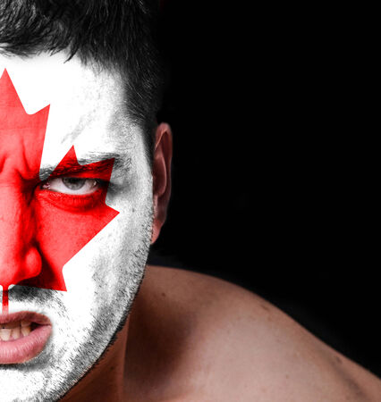 Portrait of angry man with painted flag of Canada photo