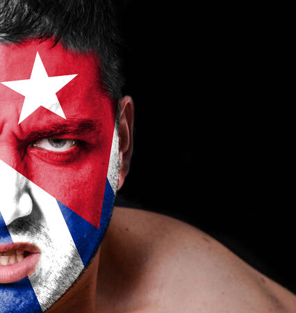 Portrait of angry man with painted flag of Cuba photo