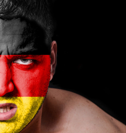 Portrait of angry man with painted flag of Germany photo