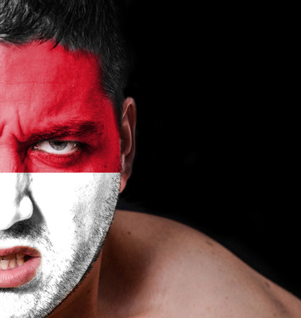 Portrait of angry man with painted flag of Indonesia photo