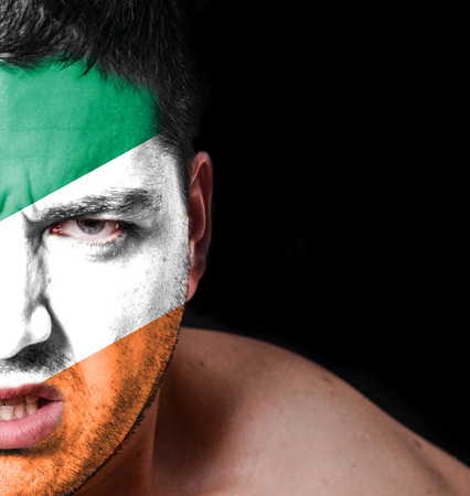 Portrait of angry man with painted flag of Ireland photo