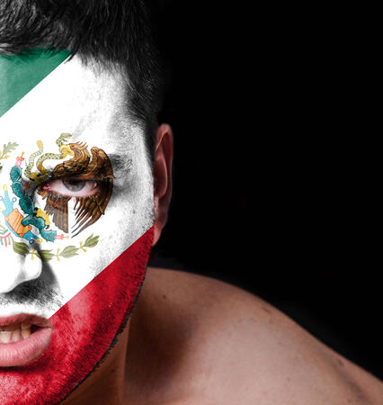 Portrait of angry man with painted flag of Mexico photo