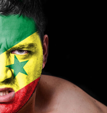 Portrait of angry man with painted flag of Senegal photo