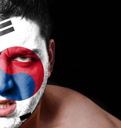Portrait of angry man with painted flag of South Korea photo