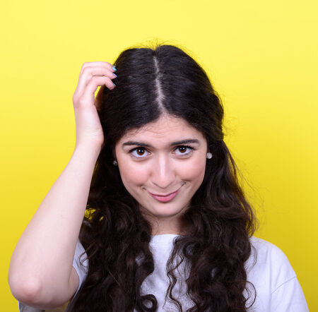 Portrait of beautiful girl thinking and scratching head against yellow background photo