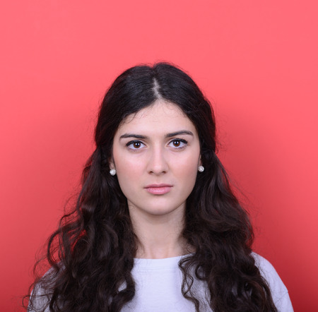 curled lip: Portrait of beautiful happy woman against red background