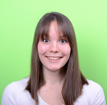 Portrait of beautiful surprised woman against green background photo