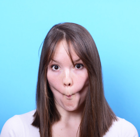 Portrait of girl with funny face against blue background photo