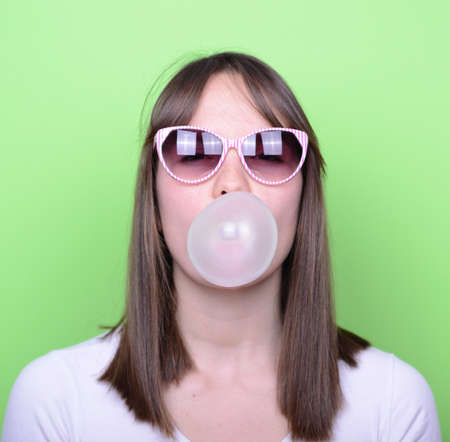 bubblegum: Portrait of girl with glasses making balloon with bubble gum