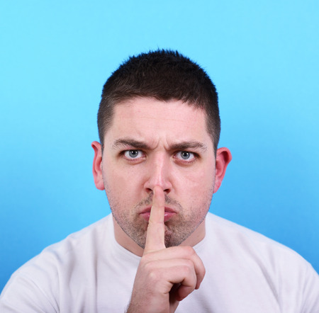 Portrait of man making silence gesture