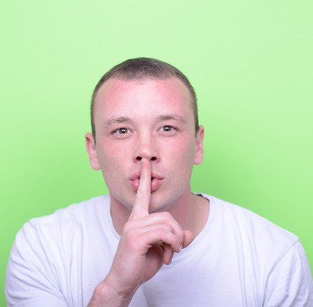 Portrait of man with gesture for silence against green background