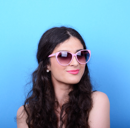 curled lip: Portrait of woman with retro glasses against blue background Stock Photo