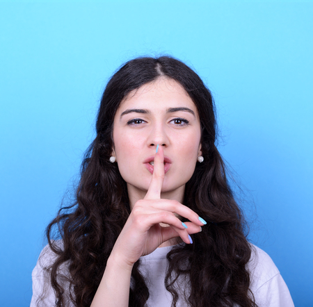 admonester: Portrait de jeune fille avec un geste de silence sur fond bleu Banque d'images
