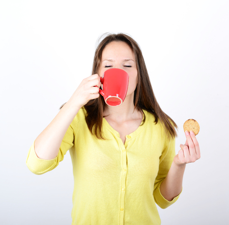 Beautiful woman holding cookies and coffee against white background photo