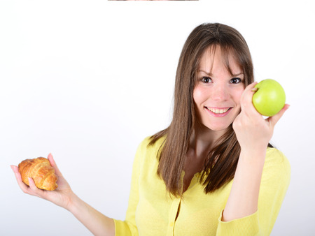 Doubtful woman holding an apple and croissant made right choice photo