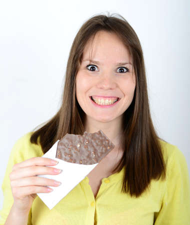 Happy woman holding chocolate bar against white background photo