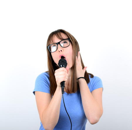 vocalist: Portrait of a young female with microphone against white background