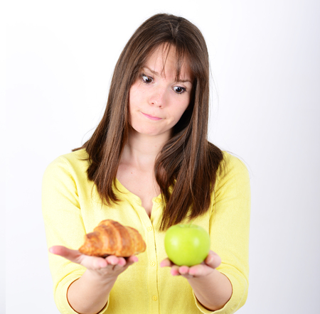 Doubtful woman holding an apple and croissant trying to decide which one to eat photo