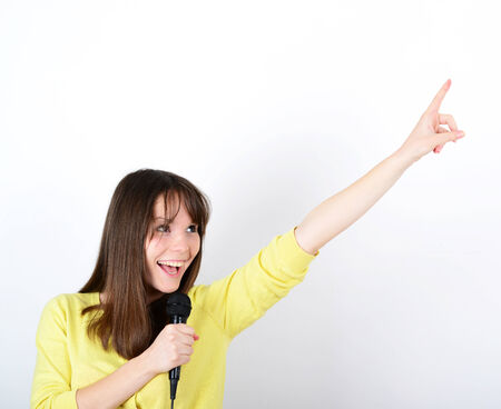 Portrait of a young female with microphone against white background