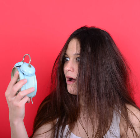Portrait of sleepy young female in chaos holding clock against red background - Running late concept