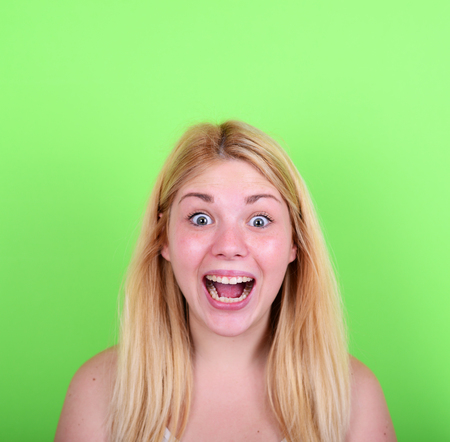 Portrait of girl with funny face against green background photo