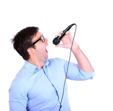 Portrait of handsome young man singing on microphone isolated on white photo