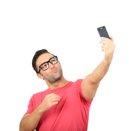 Closeup of young handsome man looking at smartphone and taking selfie photo