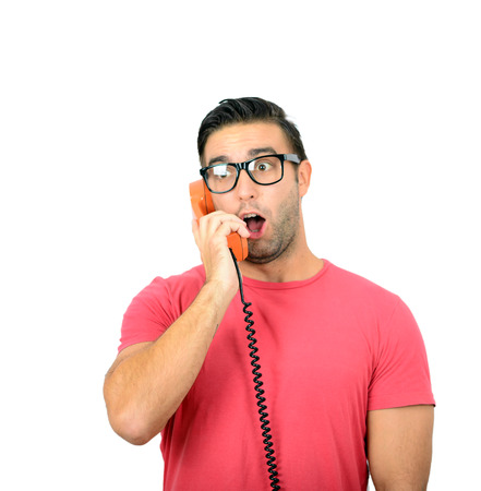 Portrait of young man yelling at phone against white background photo