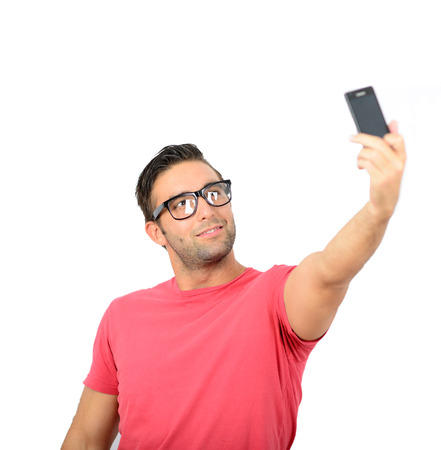 take a smile: Closeup of young handsome man looking at smartphone and taking selfie