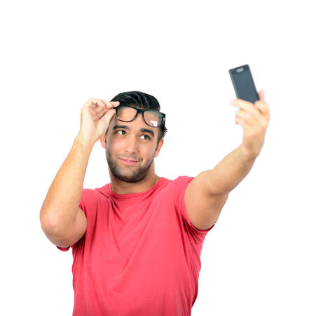 selfy: Closeup of young handsome man looking at smartphone and taking selfie