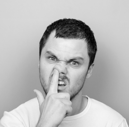 monocrome: Portrait of a funny guy with finger in his nose - Monocrome or black and white portrait Stock Photo