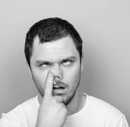 Portrait of a funny guy with finger in his nose - Monocrome or black and white portrait photo