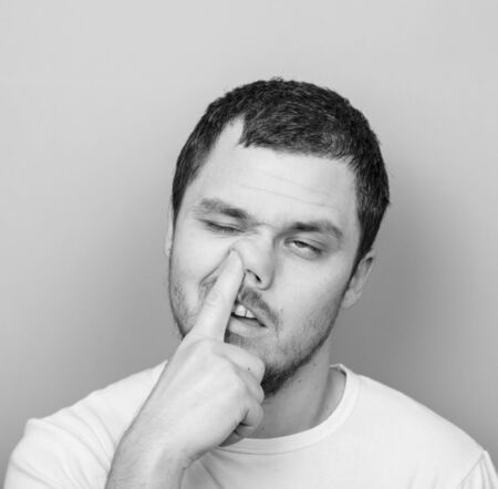 Portrait of a young man with his finger in his nose - Monocrome or black and white portrait photo