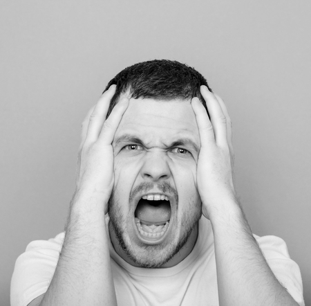 monocrome: Portrait of angry man screaming and pulling hair - Monocrome or black and white portrait