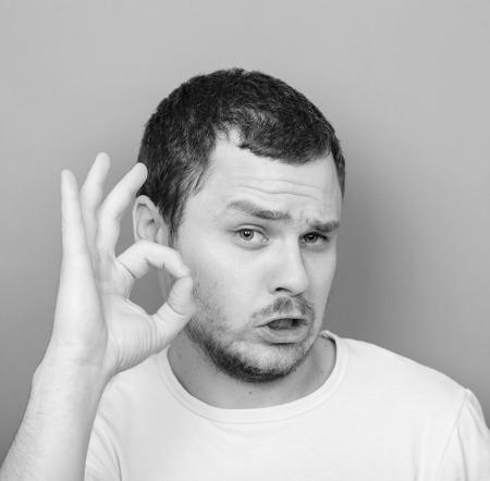 monocrome: Portrait of funny man showing OK gesture - Monocrome or black and white portrait