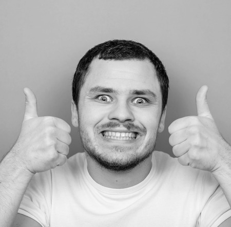 monocrome: Portrait of with funny expression holding thumbs up - Monocrome or black and white portrait