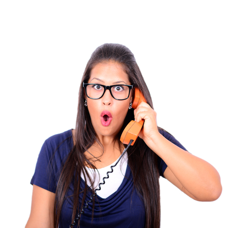 pressured: Portrait of young female in shock while talking on phone having unpleasant conversation against white background
