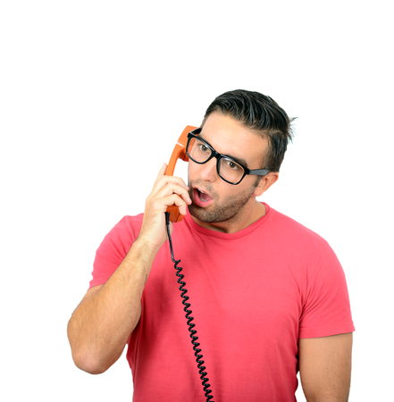 pressured: Portrait of young man in shock while talking on phone having unpleasant conversation against white background