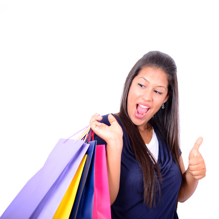 Young beautiful shopping woman on sale holding many colorful shopping bags isolated on white background photo