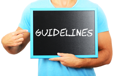guidelines: Man holding blackboard in hands and pointing the word GUIDELINES Stock Photo
