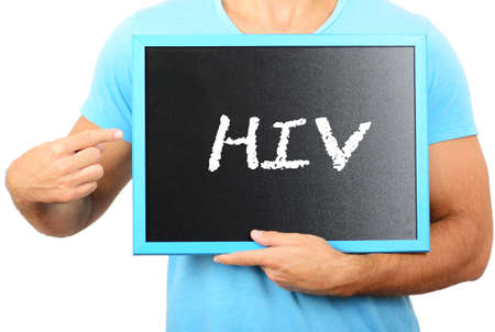 ilness: Man holding blackboard in hands and pointing the word HIV Stock Photo