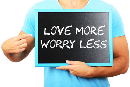 Man holding blackboard in hands and pointing the word LOVE MORE WORRY LESS