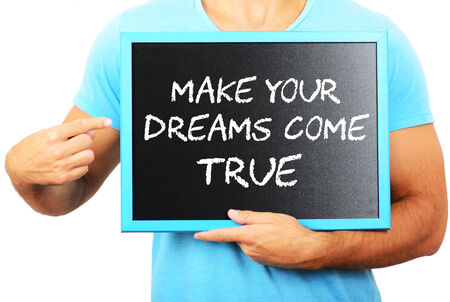 Man holding blackboard in hands and pointing the word MAKE YOUR DREAMS COME TRUE photo